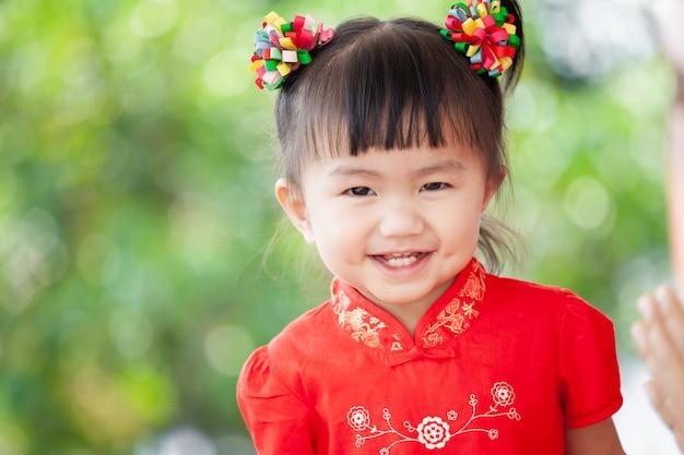 Glückliches nettes asiatisches kleines kindermädchen beim chinesischen traditionskleidlächeln