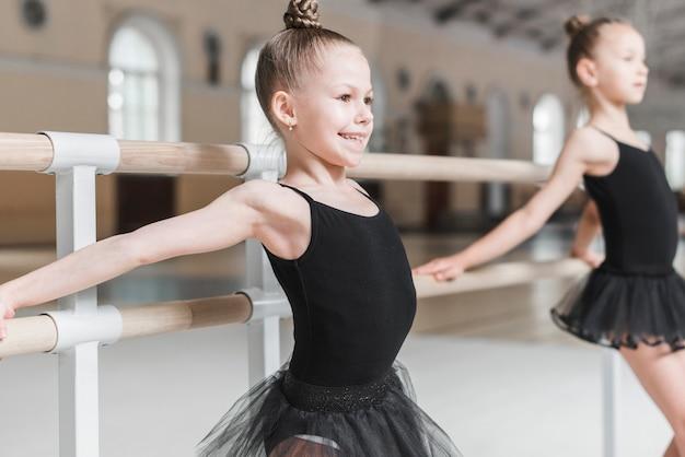 Glückliches nettes ballerinamädchen, das bei barre übt