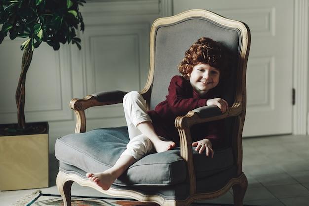 Glückliches nettes jungenkind, das weg schaut und lächelt