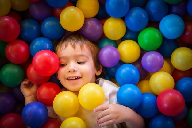 Glückliches nettes kind, das spaß am kindergarten mit bunten bällen spielt und hat
