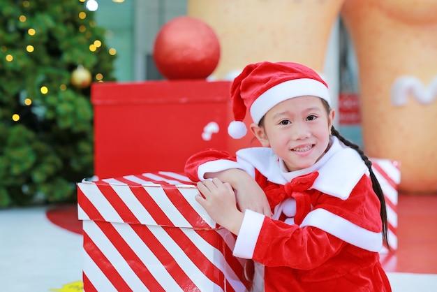 Glückliches nettes kleines asiatisches kindermädchen in sankt-kostüm mit geschenkbox nahe weihnachtsbaum und