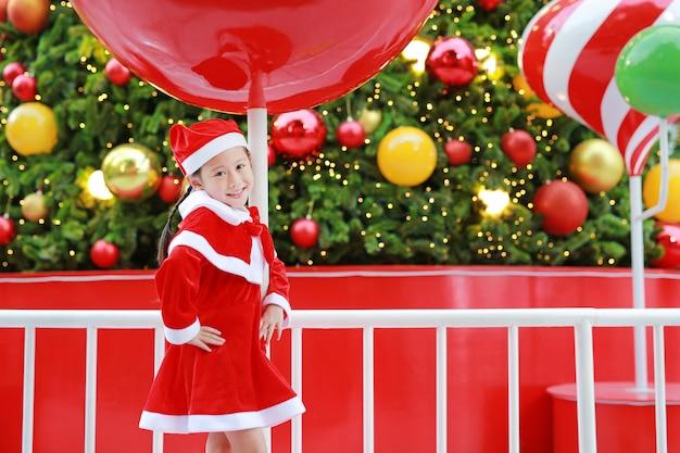 Glückliches nettes kleines asiatisches kindermädchen in sankt-kostüm nahe weihnachtsbaum und hintergrund