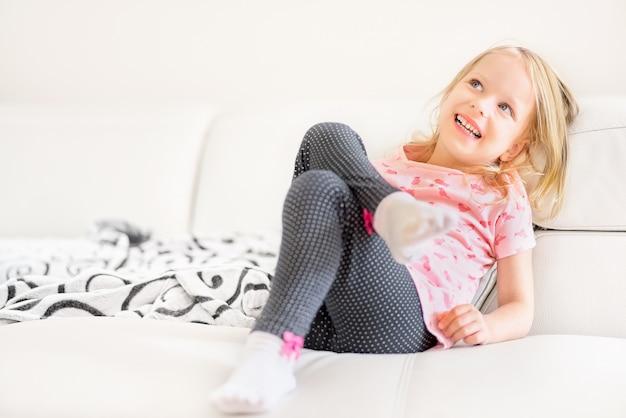 Glückliches nettes kleines blondes mädchen, verstecken sich hinter dem weißen sofa im raum zu hause, porträt