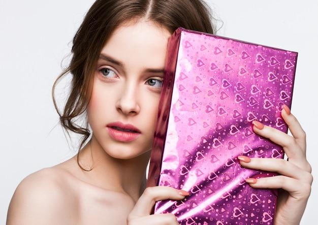 Glückliches nettes mädchen, das purpurrotes geburtstagsgeschenkboxgeschenk? n-weißhintergrund hält