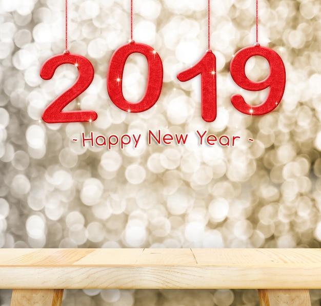 Glückliches neues jahr 2019, das über normaler hölzerner tischplatte mit unschärfengold funkelndem bokeh licht hängt