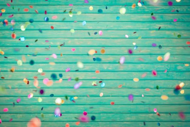Glückliches neues jahr! konfetti fällt auf holzuntergrund