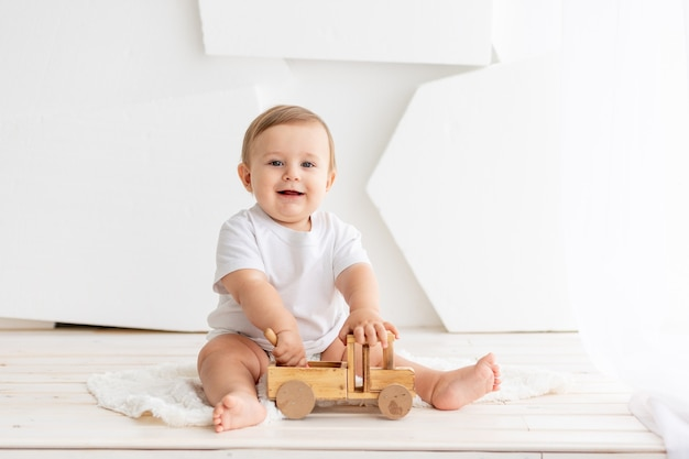 Glückliches niedliches kleines baby sechs monate alt in einem weißen t-shirt und windeln sitzt auf einem hellen hintergrund zu hause und spielt mit einer hölzernen schreibmaschine, raum für text