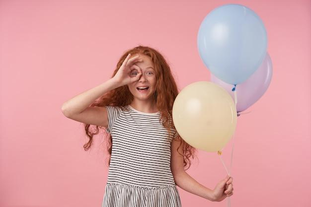 Glückliches niedliches rothaariges lockiges weibliches kind, das hand mit ok geste zu ihrem auge erhebt, über rosa hintergrund mit luftballons aufwirft, freudig zur kamera schaut und weit lächelt
