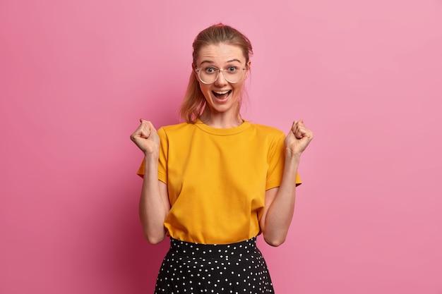 Glückliches optimistisches europäisches mädchen ballt die fäuste, freut sich über gute nachrichten, macht siegergeste, trägt transparente brille, lässiges gelbes t-shirt, erreicht ziele, feiert erfolg