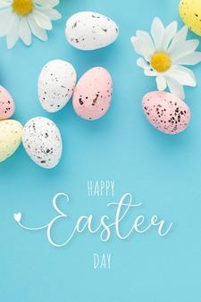 Glückliches osterplakat mit eiern und gänseblümchen auf einem blauen hintergrund