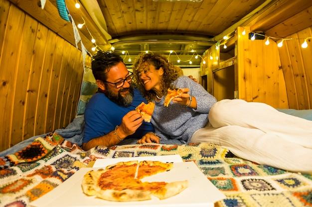 Glückliches paar alternativer reisender, die eine pizza in einem alten restaurierten, handgefertigten vintage-wohnmobil genießen