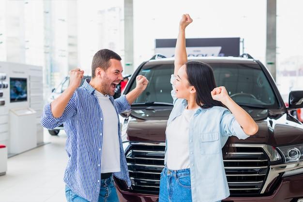 Glückliches paar am autohaus