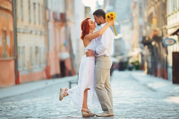 Glückliches paar, attraktive frau und mann, die in stadt gehen und romantik genießen. liebesgeschichte, paar, lächeln und viel spaß zusammen. kiev, ukraine.