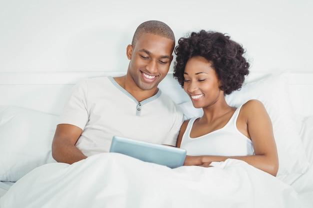 Glückliches paar auf bett unter verwendung der tablette zusammen