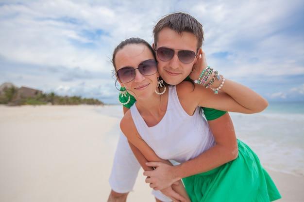 Glückliches paar auf dem exotischen strand, der kamera betrachtet