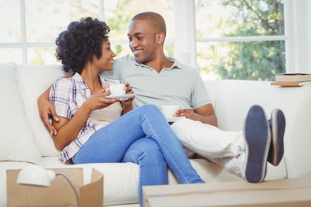 Glückliches paar auf dem sofa kaffee im wohnzimmer zu trinken
