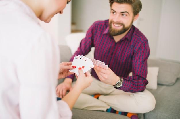 Glückliches paar auf der couch, die kartenspiel spielt