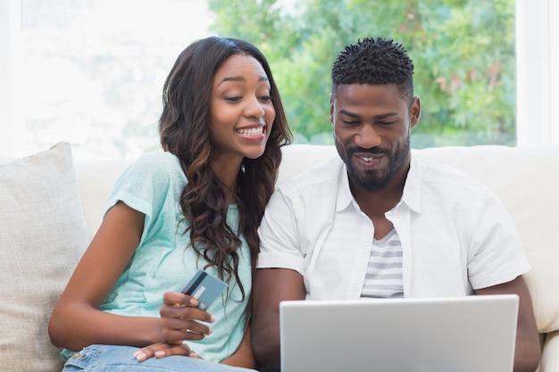 Glückliches paar auf der couch, die online kauft