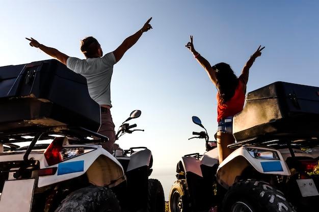 Glückliches paar auf quad-fahrrädern, die eine reise auf einem sonnenuntergangshintergrund, schattenbildfoto, rückansicht, zante genießen