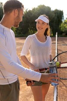 Glückliches paar auf tennisplatz