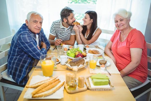 Glückliches paar beim frühstück mit ihren eltern