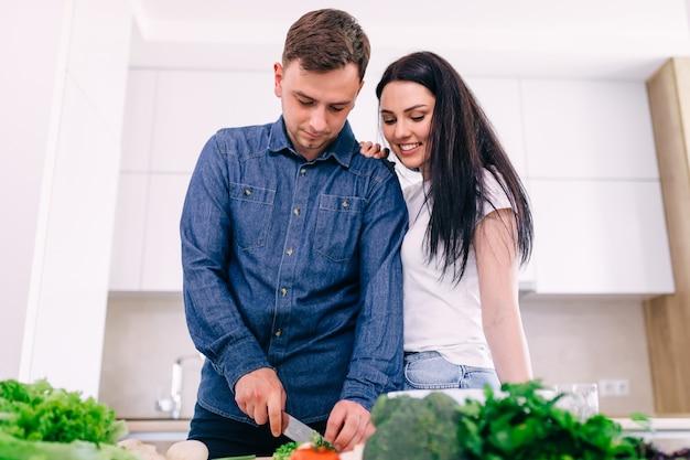 Glückliches paar bereitet köstliches mittagessen in der küche vor. mädchen, das eine tasse kaffee hält.