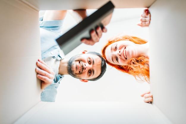 Glückliches paar, blick aus dem karton, umzug in ein neues haus. mann und frau, die pappkartons auspacken, einweihungsparty