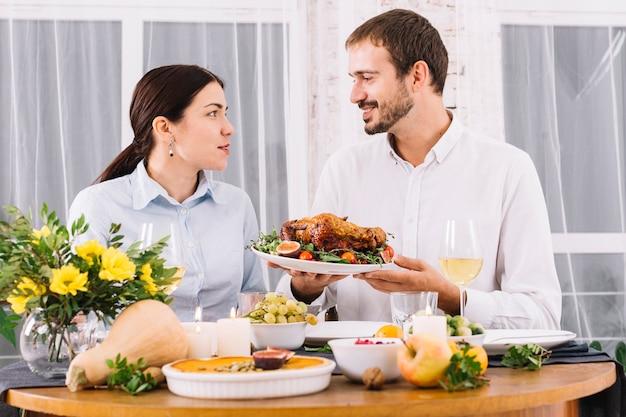 Glückliches paar, das am festlichen tisch spricht