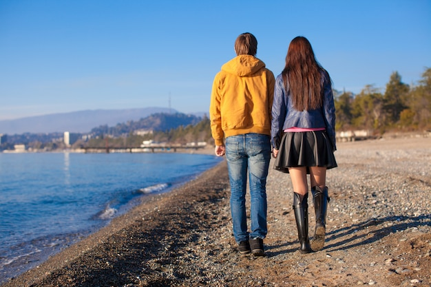Glückliches paar, das am strand an einem sonnigen wintertag geht