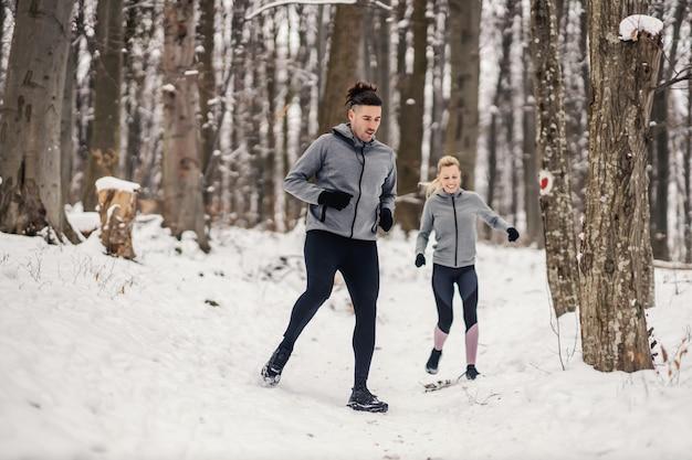 Glückliches paar, das am verschneiten wintertag in der natur läuft. spaß, gesundes leben, beziehung