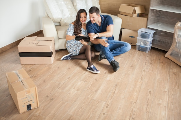 Glückliches paar, das an dekoration im neuen zuhause denkt. frohe neue familie
