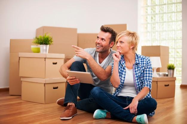 Glückliches paar, das an dekoration in neuem zuhause denkt