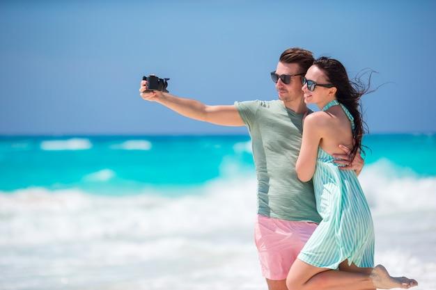 Glückliches paar, das an feiertagen ein foto auf einem strand macht