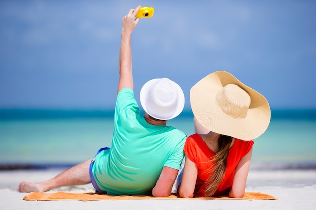 Glückliches paar, das an feiertagen ein selbstfoto auf einem strand macht