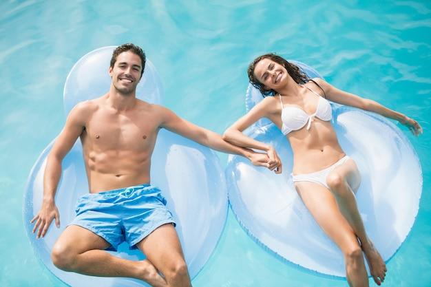 Glückliches paar, das auf aufblasbarem ring sich entspannt