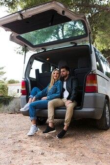 Glückliches paar, das auf autokofferraum sitzt