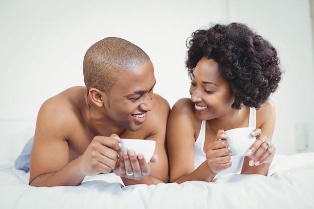 Glückliches paar, das auf bett beim halten von schalen und der unterhaltung liegt
