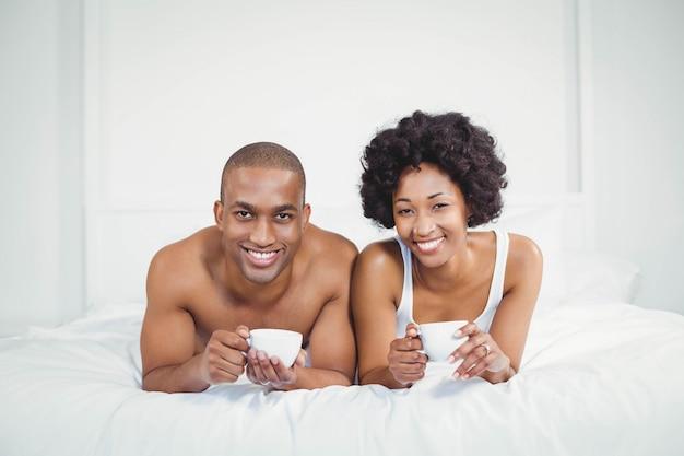 Glückliches paar, das auf bett beim schalen zu hause halten liegt