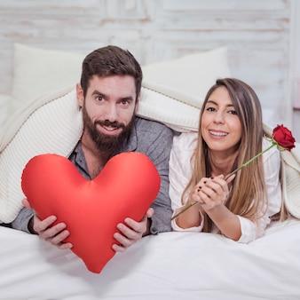 Glückliches paar, das auf bett mit weichem rotem herzen liegt
