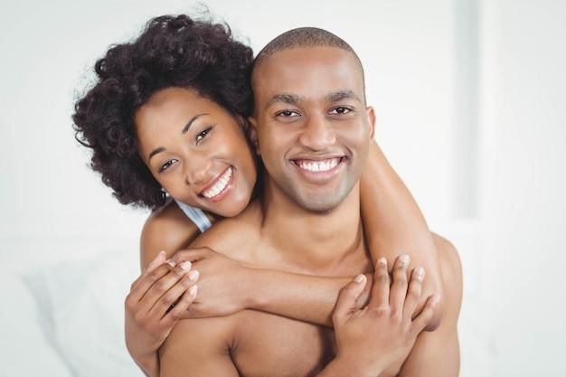 Glückliches paar, das auf bett umfasst und an der kamera lächelt