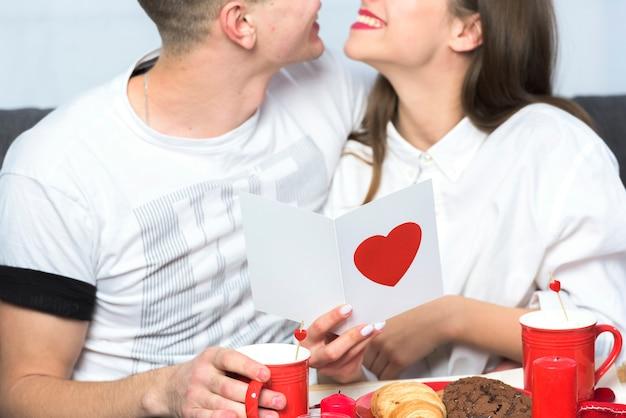 Glückliches paar, das auf couch mit grußkarte sitzt