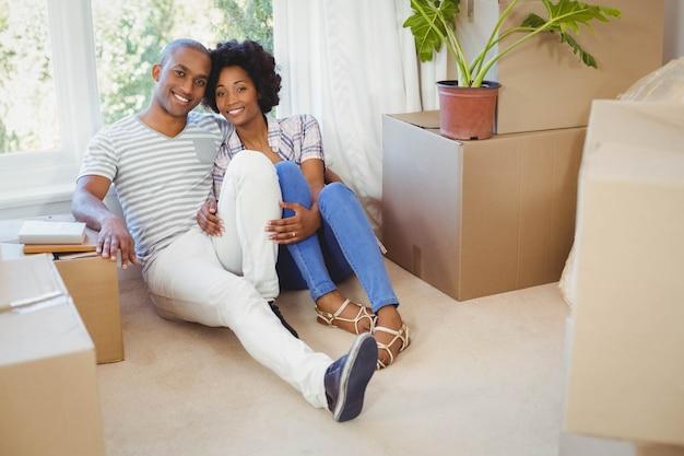 Glückliches paar, das auf dem boden im wohnzimmer sitzt