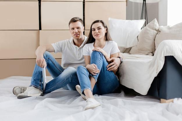 Glückliches paar, das auf dem boden in einer neuen wohnung sitzt. foto mit kopierraum