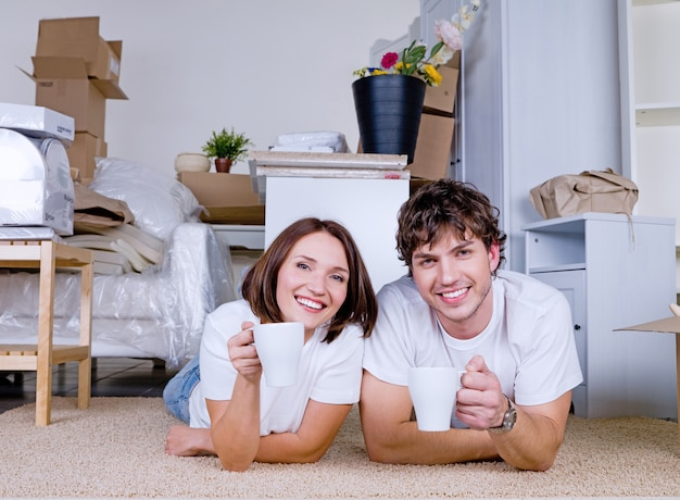 Glückliches paar, das auf dem boden mit tassen tee im neuen zuhause liegt
