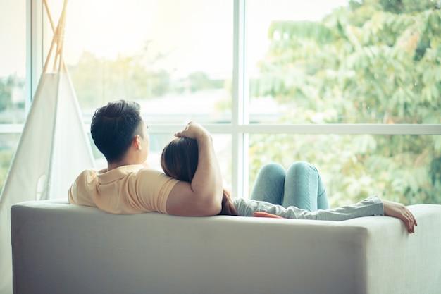 Glückliches paar, das auf dem sofa sitzt und ein mann ist, der seine freundin mit liebe im wohnzimmer umarmt und sich entspannt.
