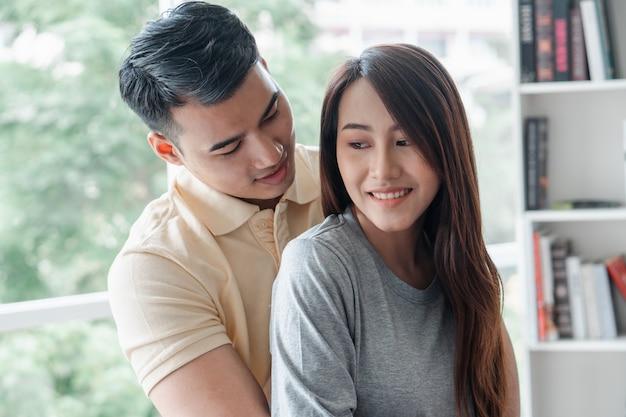 Glückliches paar, das auf dem sofa sitzt und ein mann ist, neckt seine freundin mit liebe im wohnzimmer und entspannt sich.