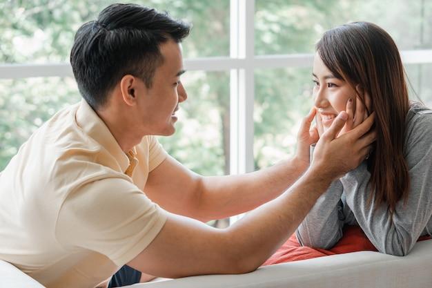 Glückliches paar, das auf dem sofa sitzt und ein mann ist, neckt seine freundin mit liebe im wohnzimmer
