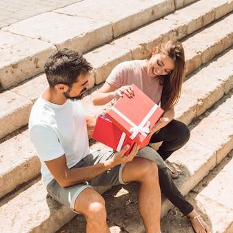 Glückliches paar, das auf dem treppenhaus öffnet rote geschenkbox sitzt