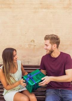 Glückliches paar, das auf der bank hält geschenk sitzt