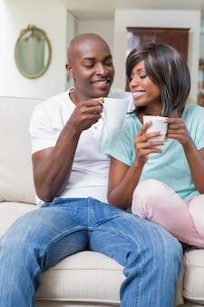 Glückliches paar, das auf der couch kaffee trinkend sich entspannt